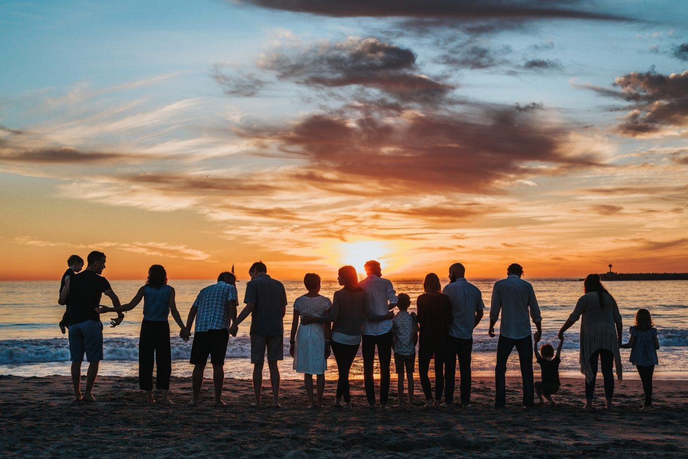 Large family holds hands while looking at sunset over beach