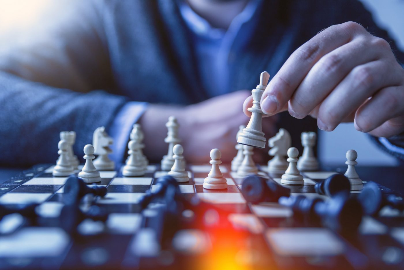 man moves bishop across chessboard
