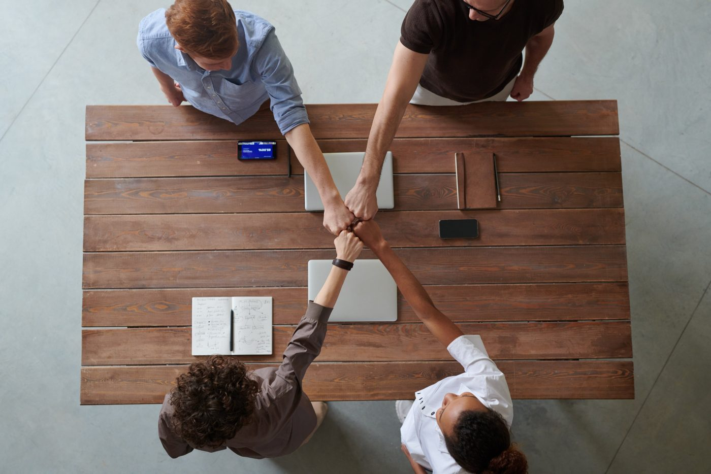 Four people fist bump over table of desk work