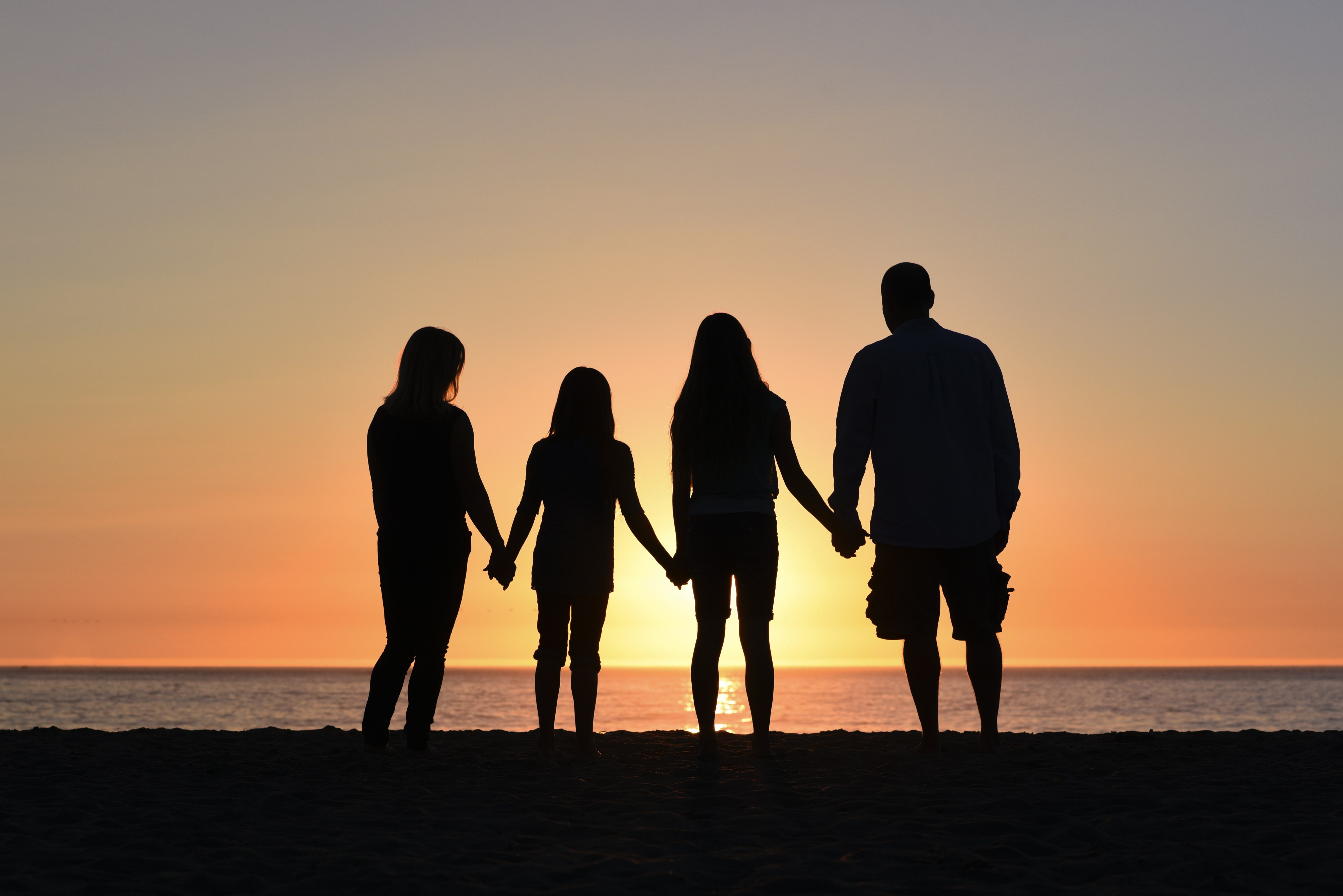 family holds hands while looking at sunset over beach